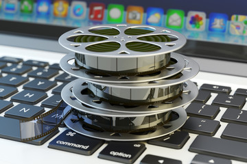 Online movies cinema concept, internet video and  multimedia content, stack of film reels on computer laptop keyboard