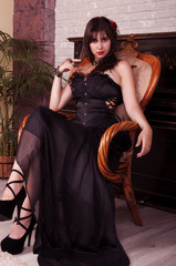 Sexy woman in black dress sitting near piano.