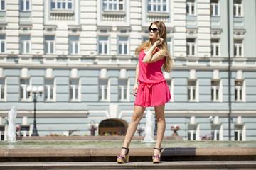 Young beautiful woman in red short dress posing outdoors in sunn