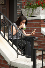 Woman having a coffe in front of her house on the stairs