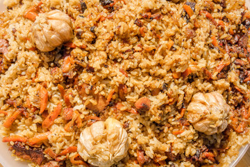 close up view of plov with meat, rise, garlic, onion, carrot and spices