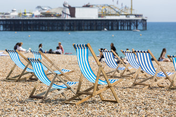 Traditional old-fashioned blue and white striped deckchairs on the beach in front of the Palace Pier, Brighton, East Sussex, UK