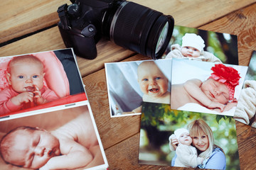 Children's photos and camera on a wooden background.