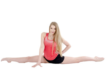 Beautiful long-haired cheerful girl is engaged in gymnastic exercises on the floor