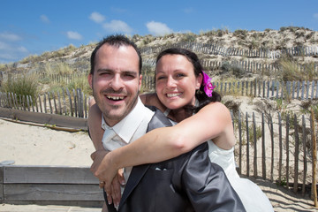 Wedding couple in love at the beach , piggy back