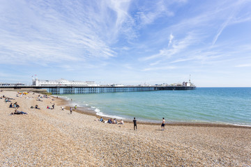 The shingle beach at Brighton, East Sussex, UK in summer and the Palace Pier (Brighton Pier) with holidaymakers sunbathing on a sunny day under a blue sky and wispy clouds