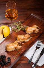 Three fried quails stuffed with prunes with white wine