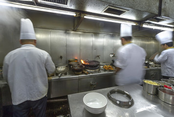 Crowded kitchen, a narrow aisle, working chef.