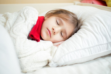 portrait of cute girl in sweater and scarf lying on white pillow