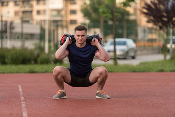 Young Man Doing Bag Squat Exercise Outdoor