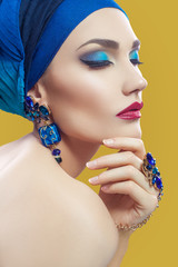 Beautiful middle eastern woman with hijab with blue scarf and blue jewelry and red lips on yellow background, studio shot. with closed eyes.
