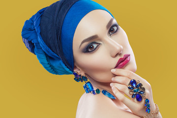 Beautiful middle eastern woman with hijab with blue scarf and blue jewelry and red lips on yellow background, studio shot. looking at camera.