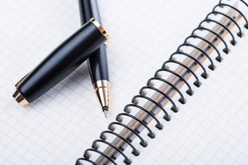 A spiral notebook with black ball pen over the white background, isolated
