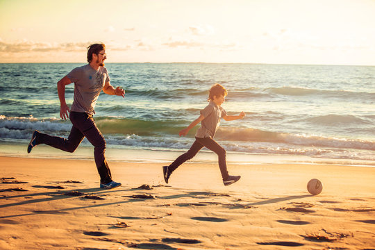 Happy father and son play soccer or football on the beach in