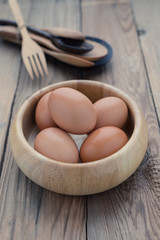 The eggs in the wooden bowl with spoon and fork