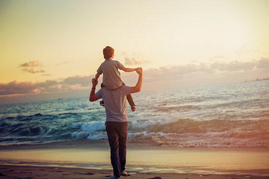 Happy father and son having great time on the beach in sunset
