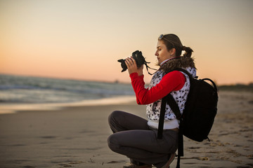 Girl photographer taking pictures with SLR camera at sunset on