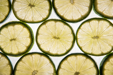 Lime slices on parchment paper, back-lit and glowing