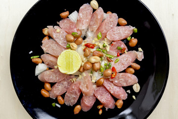 Closeup Thai sour pork sausage salad in black plate