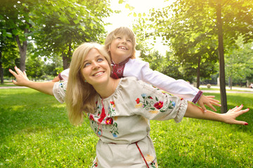 Portrait of happy ucrainian mother and son in summer park, outdo