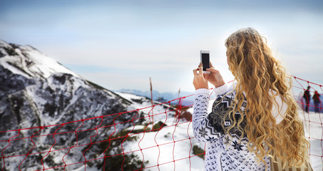 Woman photographing winter landscape mountains and snow with cel