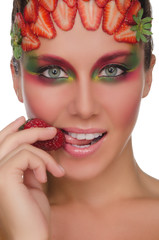 Beautiful woman with strawberries on face and hand