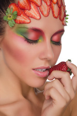young woman with strawberries on face and hand