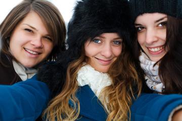 Girls taking selfie outdoors in winter.