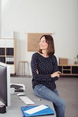 entspannte mitarbeiterin sitzt auf dem schreibtisch