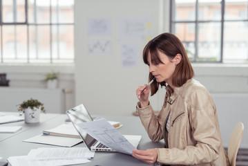 mitarbeiterin im büro schaut auf bauplan