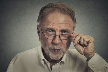 senior elderly skeptical man with eyeglasses