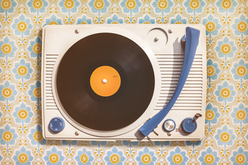 Vintage record player on top of flower wallpaper