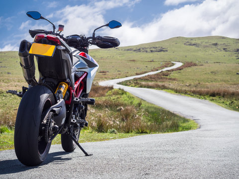A supermotard type motorcycle facing towards the winding road ahead