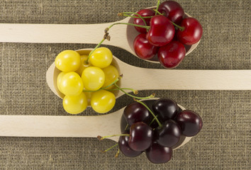 Colorful cherries in a wooden spoon on a natural fabric