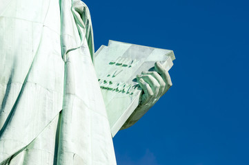 July 4, 1776 Independence Day tablet held by the Statue of Liberty close-up against bright blue sky