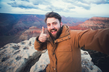 Handsome bearded man makes selfie photo on travel hiking at Grand Canyon viewpoint in Arizona, USA
