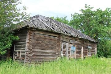 Разрушенный дом в заброшенной деревне на поле летом