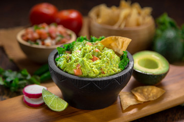 Mexican restaurant style side of Guacamole food and chips on a wood cutting board vertical shot with salsa