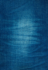 background texture of blue jeans with pleats and scuffed