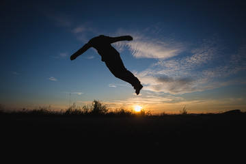 Wall Mural - man jumping in sunset