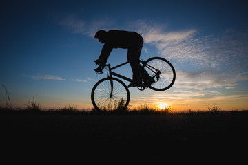 cyclist doing nose wheelie with race bike in sunset