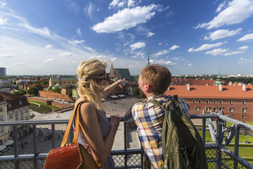 Young couple of tourists standing on the observation platform of the Castle Square in Warsaw, Poland.