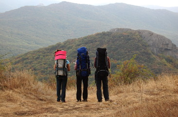 Three tourists with backpacks stand on a mountain slope.