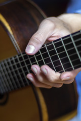 Male's hand on a classical guitar fretboard