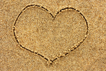 Heart drawn in the sand on a sunny day