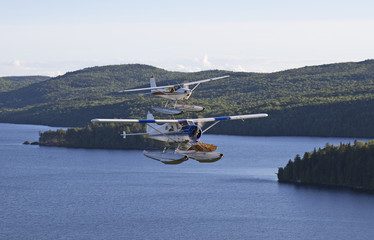 Two water plane flying side to side over a lake