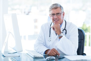 Smiling doctor working on computer at his desk