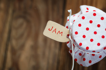 top view on jar of jam with strawberry  and noties on wood background