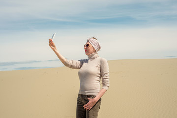 Woman catches link on the smartphone in the desert