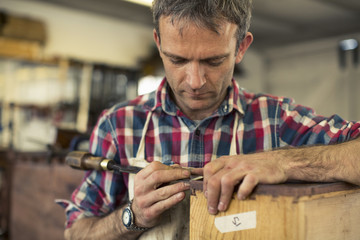 An antique furniture restorer working with his hands using a sharp tool on the edge of a piece of wooden furniture.